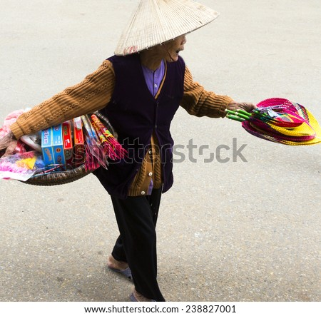 Vietnamese Woman Selling Fireworks Hanoi Vietnam - November 10 2014: Old Vietnamese Woman Selling Colorful Fireworks and Incense on Streets of Hanoi - stock photo