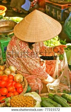 Vietnamese woman selling vegetables on the market street, Hanoi, Vietnam