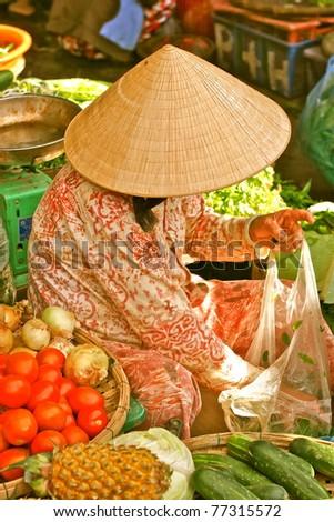 Vietnamese woman selling vegetables on the market street, Hanoi, Vietnam - stock photo