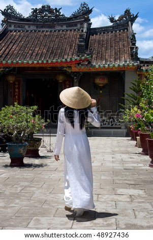 Vietnamese Woman wearing a Ao-Dai costume in front of a Temple