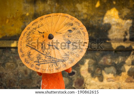 Vietnamese woman wearing traditional clothes with yellow paper umbrella - stock photo