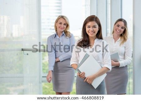 Vietnamese young business lady standing in front of team