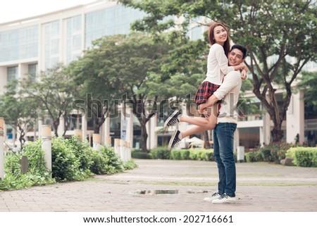 Vietnamese young man carrying his beautiful girlfriend - stock photo