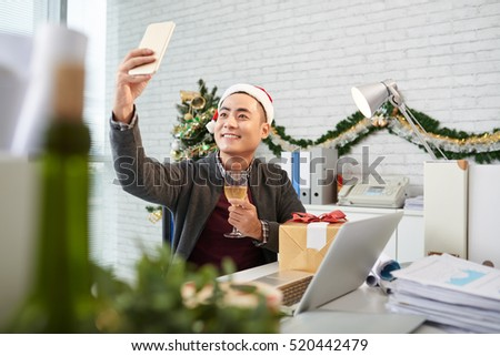 Vietnamese young man taking selfie in office decorated for Christmas