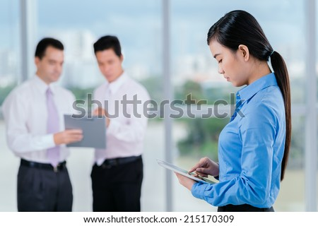 Vietnamese young manager using digital tablet while her male colleagues talking in background - stock photo
