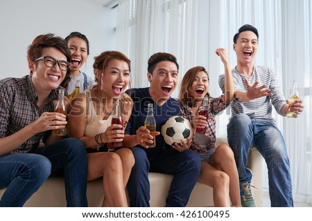 Vietnamese young people cheering for their favorite soccer team - stock photo