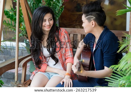 Vietnamese young woman playing guitar for her girlfriend - stock photo