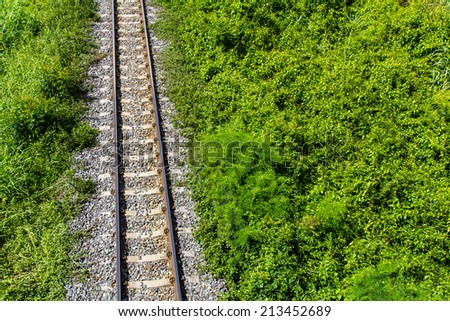 View above the railroad tracks with grass growing on the side - stock photo