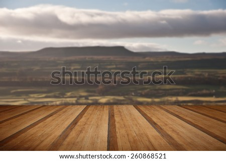 View across fields towards Pen-y-Ghent in Yorkshire Dales National Park with wooden planks floor - stock photo