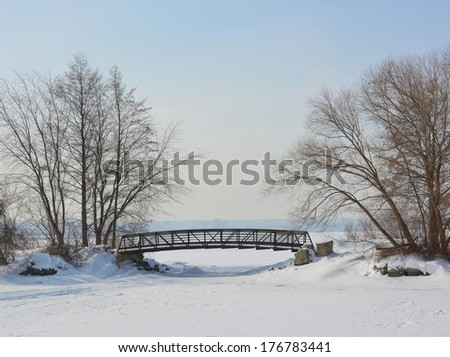 view across frozen lake Ontario towards a footbridge with Hamilton in the misty background, Lasalle park in Burlington, Ontario  - stock photo