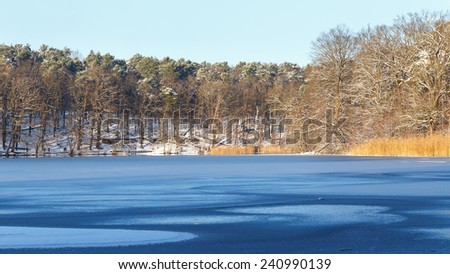 View across partially frozen Lake Schlachtensee in Berlin, Germany in winter. - stock photo