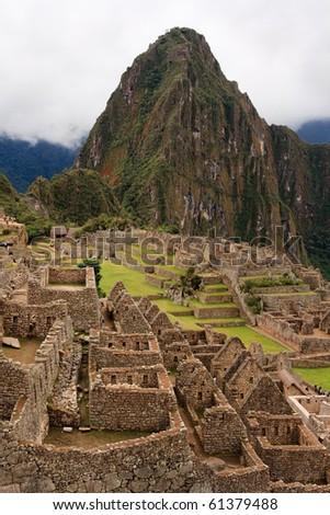 View across the ancient inca ruins of Machu Picchu in Peru, wayna picchu in background - stock photo