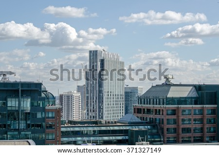 View across the City of London towards Spitalfields and a tower block of student accommodation.  Seen from a tall building on a sunny afternoon in September. - stock photo