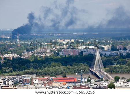 View across the city of Poland with the Syrena bridge and a distant fire putting smoke and pollution into the air - stock photo