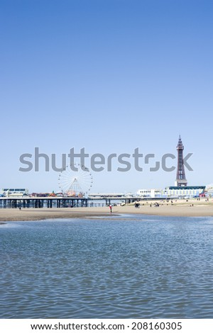 View across the sea of the waterfront and beach with the Blackpool Tower and piers, Blackpool, England - stock photo