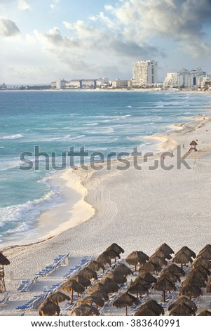View along a curving beach of the brilliant blue ocean and distant hotels in Cancun, Mexico