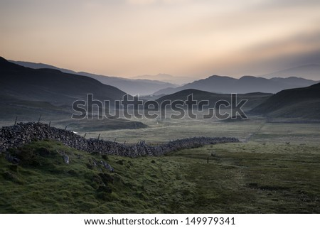 View along countryside fields towards misty Snowdonia mountain range in distance - stock photo