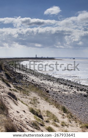 View along Spurn Point coastline with lighthouse, nature reserve, east yorkshire, UK - stock photo