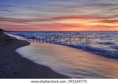 View along the Cottlesloe beach in Perth, Western Australia. Spectacular sunset over Indian ocean with bright pink shades in clouds and blurred waves over sand. - stock photo