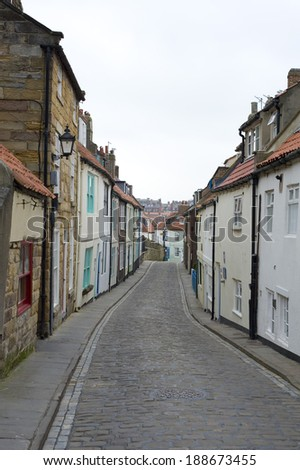 View along the length of the narrow cobbled Henrietta Street, Whitby, North Yorkshire with its traditional historical English cottages - stock photo