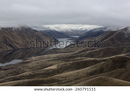 View along the Snake River Canyon between Idaho and Oregon in the Magic Valley Region in winter with snow capped mountains and cloud cover - stock photo