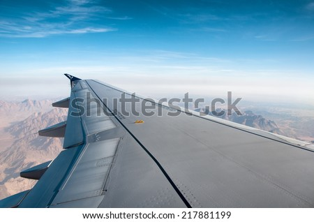 View along the wing of an airplane from the passengers perspective flying over mountainous terrain with a hazy sunny blue sky above - stock photo