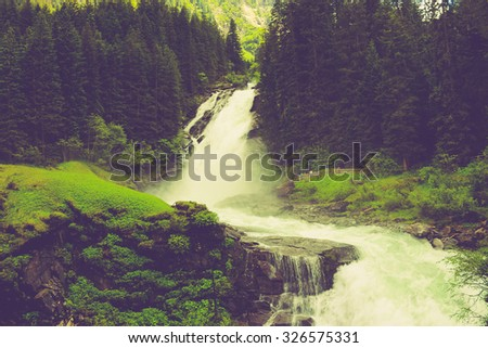 View Alpine inspiring Krimml waterfall curve in mountains, blue sky, deep rich green forest, spruce, trees. Summer. trekking in National park Hohe Tauern, Austria. poster Image instagram filter photo - stock photo