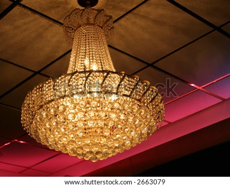 View at an angle of a lighted chandelier. - stock photo