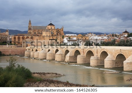 View at ancient Cathedral and bridge across Guadalquivir river in Cordoba, Spain - stock photo
