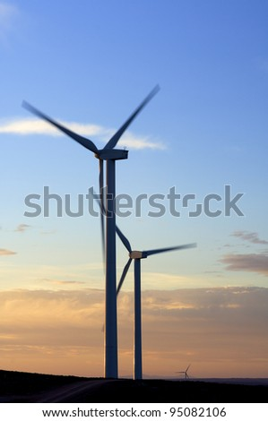 view  at dusk of two windmills for renewable electric energy production