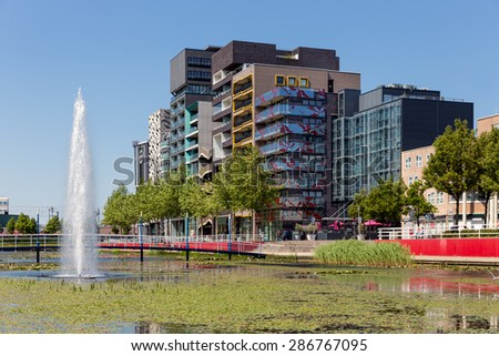 View at modern apartments and office buildings with pond and fountain in front of it, Lelystad, the Netherlands