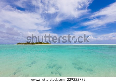 view at perfect tropical island, surrounding turquoise lagoon and blue sky - stock photo