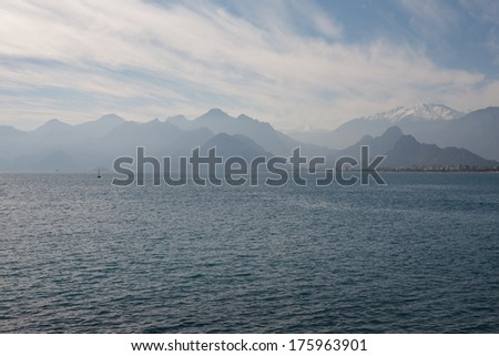 view at the beautiful mountains of antalya turkey with the ocean or sea water in the foreground and blue clouds above