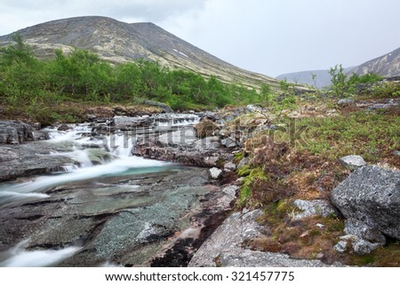 View at the mountains and river stream of melt water flowing from the peaks, long exposure - stock photo