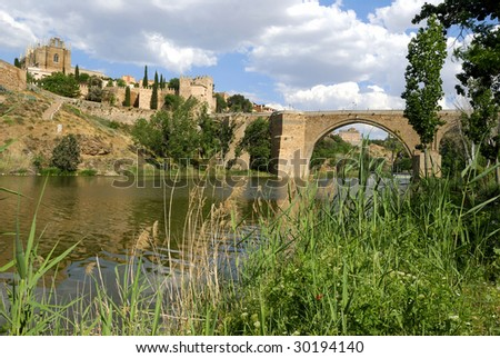 View at the old city of Toledo in Spain with bridge over the Tagus river. The city at the inner side of the wall is an UNESCO World Heritage site. - stock photo