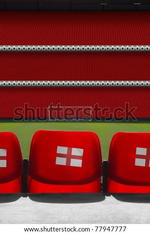 view behind empty seats at a empty football stadium with the england St George's flag on the back of the seats - stock photo