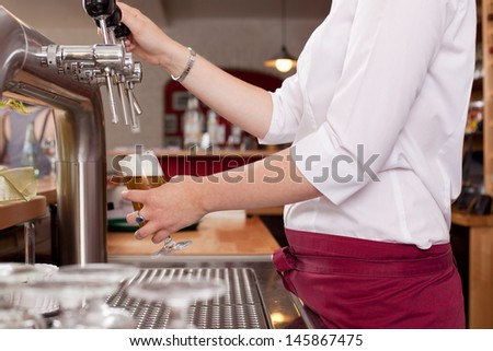 View behind the counter of the hands of a woman dispensing draft beer in a bar from a row of metal spigots - stock photo