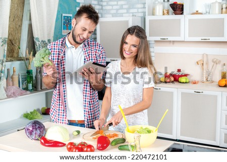 View cooking recipe. Young and beautiful couple in love food cooking according to the recipe on the tablet while they are preparing breakfast in the kitchen. - stock photo