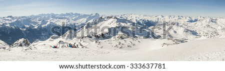View down a snowy piste with skiers relaxing and view over mountain valley - stock photo