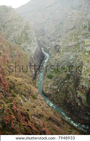 View down from the top of Royal Gorge canyon, kayakers in the mountain stream - stock photo