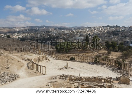 View down onto the Oval Plaza in the ancient Roman city of Jerash, Jordan. You can see the modern city of Jerash in the background. - stock photo