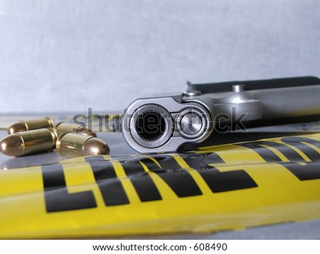 View down the barrel of a .45 handgun, with crime scene.