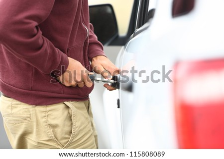 View down the length of a car to a man committting a car break in and theft with a screw driver inserted into the lock - stock photo