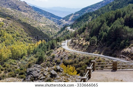 View down the winding A337 road from the Puerto de la Ragua mountain pass over the Sierra Nevada mountains in Andalucia, Spain - stock photo