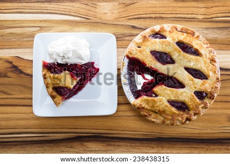 view form above of a fresh baked cherry pie with a slice on a white plate