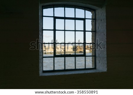View framed by black surrounding wall to recent architectural buildings on other side River Thames through old wharf warehouse building windows from the dark interior at Wapping, London