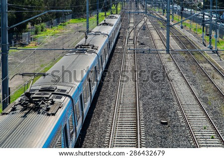 View from a bridge of an electric suburban train passing underneath.  The train is a Melbourne suburban train in Australia but no signage is visible on the train. - stock photo