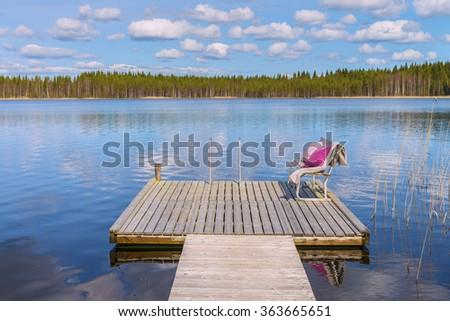 View from a height at the wooden pier and cozy bench with soft blanket and pillows on a background of the beautiful lake and forest at sunny day.Panoramic view.The land of lakes.Finland.Europe. - stock photo