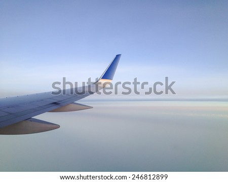 View from a jetliner of its right wing over creamy smooth clouds.