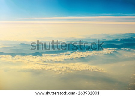 View from a plane to sunset on the sky with sunrays. Fluffy clouds background - stock photo